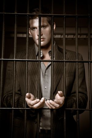 A caucasian businessman sitting in jail handcuffed photo