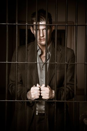 A caucasian businessman sitting in jail handcuffed