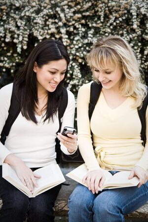 A shot of two college students texting text messages on campus Banco de Imagens