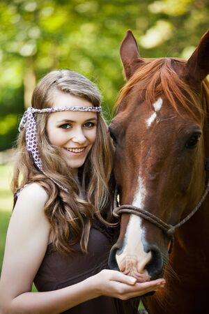 A portrait of a caucasian girl with her horse photo