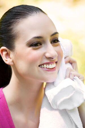 haciendo ejercicio: Una bella mujer que hace ejercicio caucasian limpia su sudor fuera Foto de archivo
