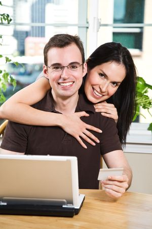 A happy couple holding a credit card shopping online Stock Photo - 5255640
