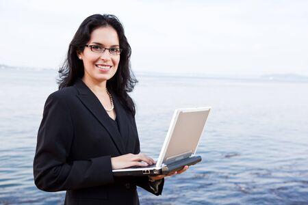 A portrait of a hispanic businesswoman holding a laptop outdoor