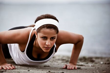 A beautiful asian woman doing push up at a beach photo