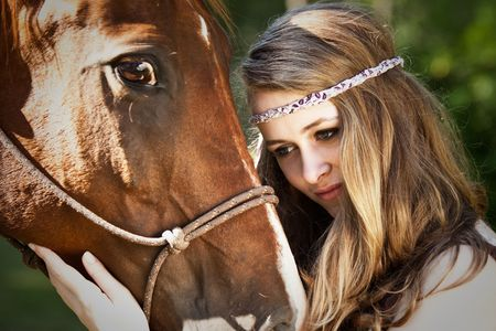 A portrait of a caucasian girl with her horse