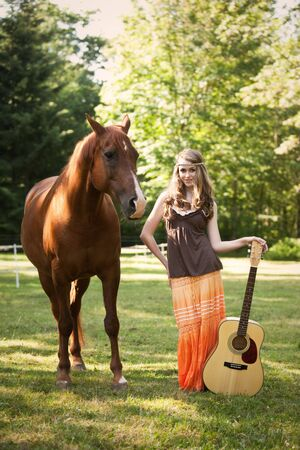 A portrait of a caucasian girl with her guitar and her horse photo