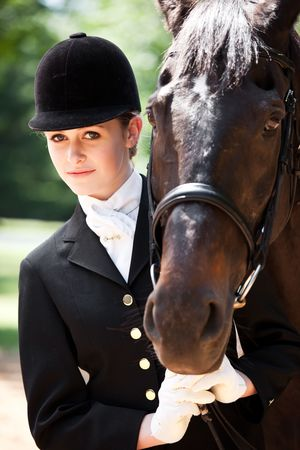 A caucasian girl getting ready for a horseback riding posing with her horse photo