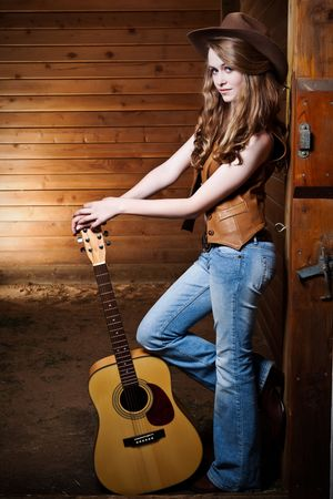 A portrait of a happy beautiful caucasian cowgirl with a guitar photo