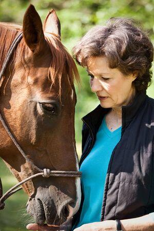 mujer en caballo: Una foto de una mujer blanca altos con su caballo Foto de archivo