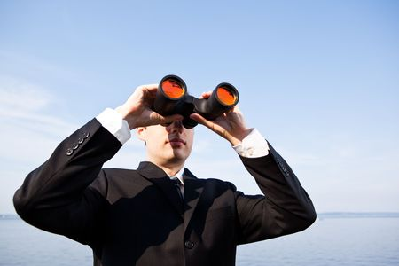 A portrait of a caucasian businessman looking through binoculars  outdoor Stock Photo