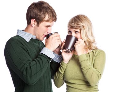 women holding cup: A portrait of a happy beautiful caucasian couple holding coffee cups