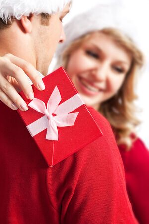 A portrait of a happy cute caucasian girl receiving a surprise christmas gift from his boyfriend (focus on the gift box) Stock Photo