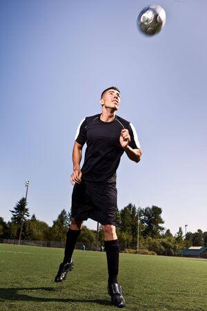 A shot of a hispanic soccer or football player heading a ball photo