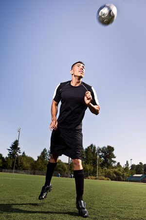 A shot of a hispanic soccer or football player heading a ball
