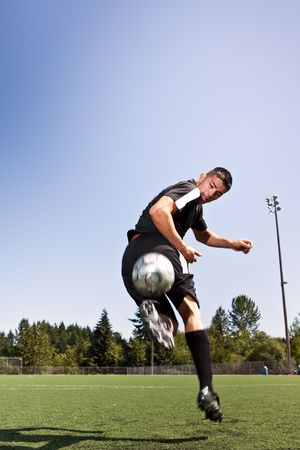 A shot of a hispanic soccer or football player kicking a ball photo