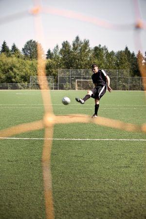 A shot of a hispanic soccer or football player kicking a ball Stock Photo - 5545073