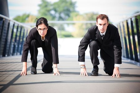 A shot of two business people in a running start position competing against each other photo
