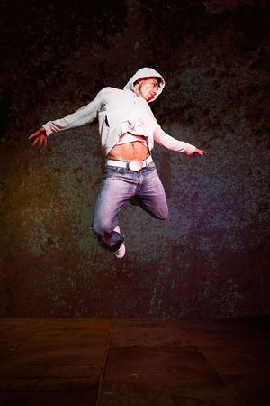 A shot of a hispanic male doing a hip-hop dance jumping in the air photo