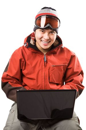 An isolated shot of an asian snowboarder typing on the laptop photo