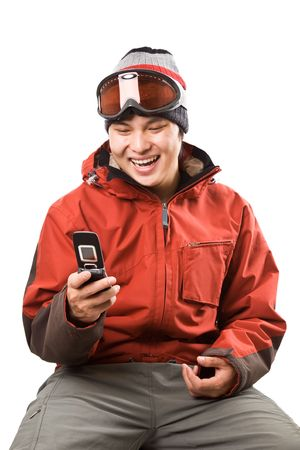 An isolated shot of an asian snowboarder texting with his cellphone photo