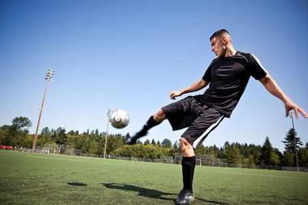 A shot of a hispanic soccer or football player kicking a ball Banque d'images