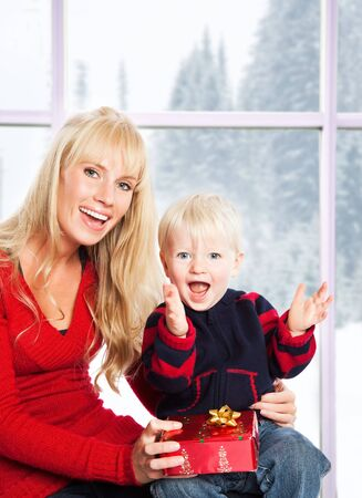 A caucasian mother and son opening christmas gifts photo