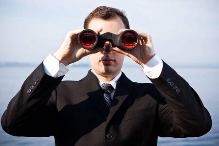 A portrait of a caucasian businessman looking through binoculars  outdoor photo