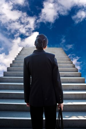 A conceptual shot of a businesswoman at the bottom of the stairs photo
