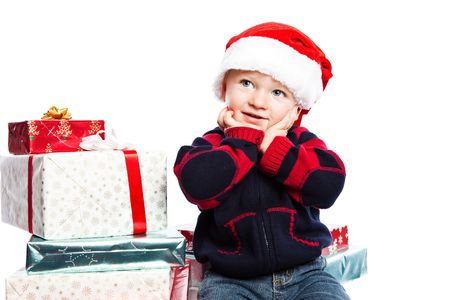 A caucasian boy wearing a santa hat with a lot of christmas gift photo