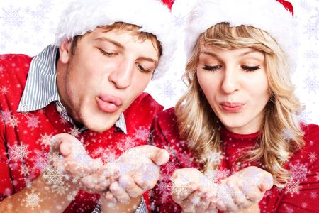 happy christmas: A portrait of a happy  caucasian christmas  couple blowing snowflakes Stock Photo