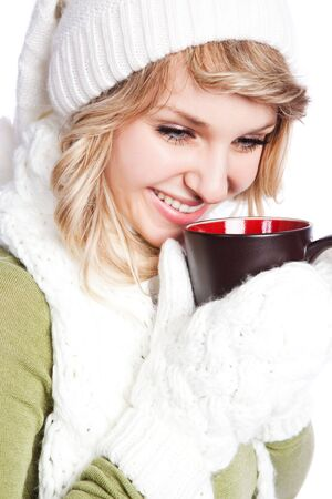 women holding cup: A portrait of a happy beautiful caucasian winter woman holding a coffee cup Stock Photo