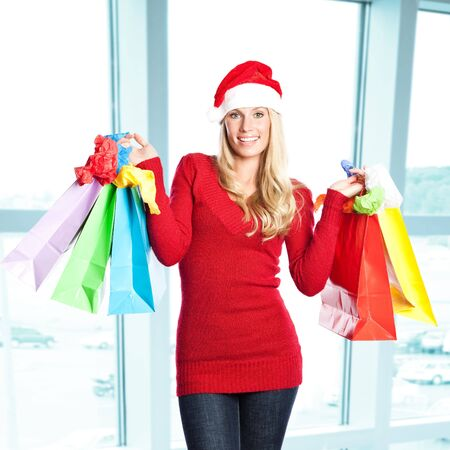 sales person: A portrait of a beautiful caucasian christmas santa girl carrying shopping bags Stock Photo