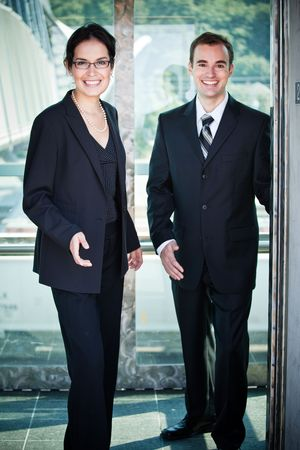 A shot of two happy business people coming out from the elevator photo