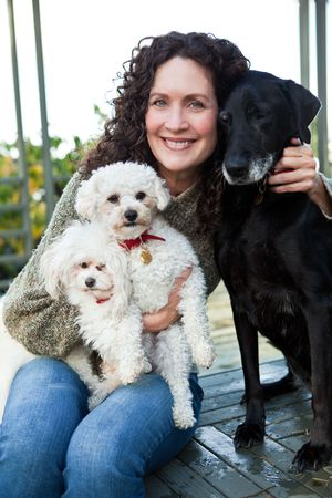 A portrait of a happy mature woman with her dogs outdoor photo