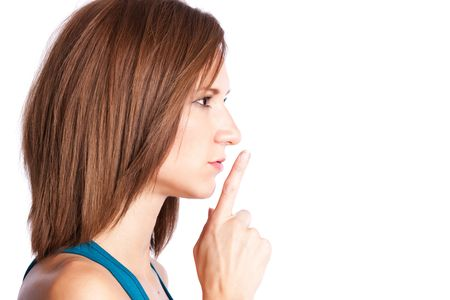 shutup: A portrait of a woman shushing with her finger on her lips Stock Photo