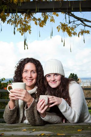 A portrait of a happy mother and daughter drinking coffee outdoor photo