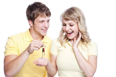 joy of giving: An isolated shot of a young caucasian couple holding a set of keys
