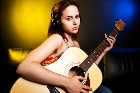 A shot of a beautiful caucasian woman wearing headphones and holding a guitar photo