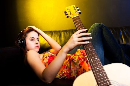 A shot of a beautiful caucasian woman lying down on the sofa listening music with headphones photo