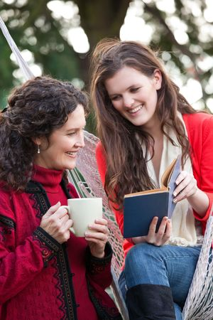 A portrait of a happy mother and daughter reading a book outdoor photo