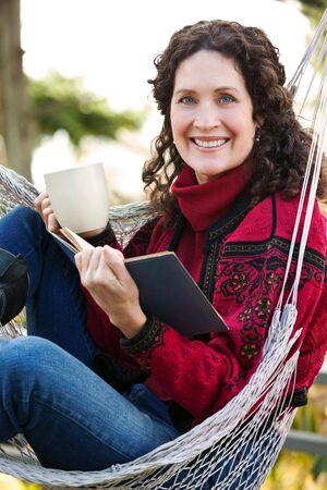 winter woman: A beautiful mature woman sitting on a hammock reading a book