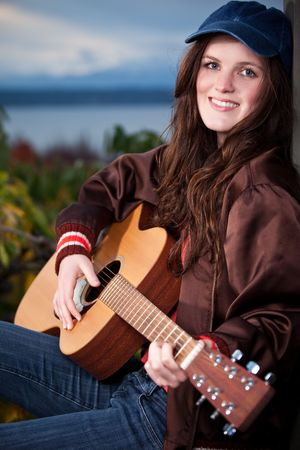 A portrait of a beautiful teenager playing guitar Stock Photo - 6229815