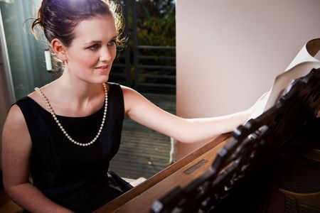 A portrait of a beautiful teenager playing piano photo