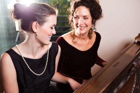 tocando el piano: Un retrato de una madre feliz y su hija juntos tocando el piano