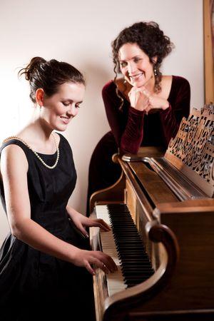 tocando piano: Un retrato de una madre feliz y su hija juntos tocando el piano