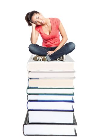 An isolated shot of a beautiful black college student sitting on a stack of books photo