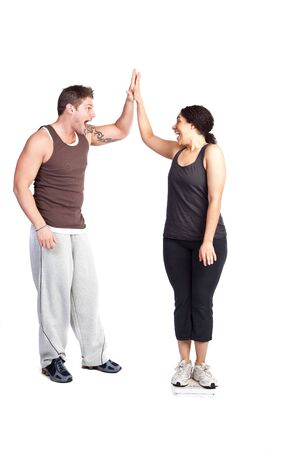 weightloss: A happy woman standing on a weight scale celebrating with her personal trainer Stock Photo