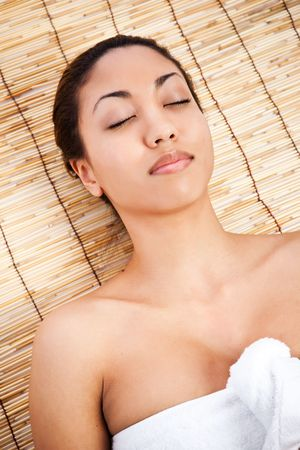 A shot of a black woman lying down at a spa photo