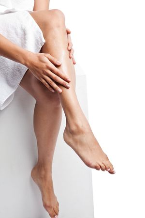 An isolated shot of a beautiful black woman applying  lotion on her legs Stock Photo - 6271546