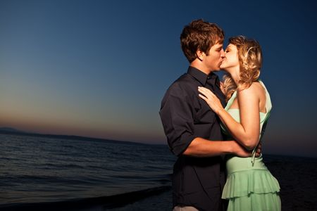 A romantic caucasian couple in love kissing on the beach photo